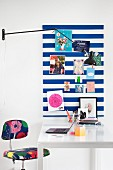 Striped pinboard above white desk and colourful accessories