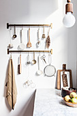 Utensils hung from hook rails in kitchen with wooden cabinets