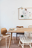 Various wooden chairs around simple dining table below artwork on wall