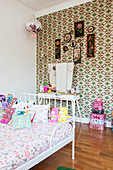 Scatter cushions and soft toys on white bed in girl's bedroom with retro wallpaper