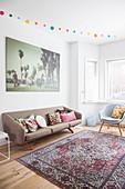 Retro Sofa mit Kissen, darüber großformatiges Foto im Wohnzimmer