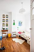 Blick ins Kinderzimmer mit Bett und kleinem Schreibtisch