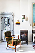 Antique wardrobe with mirror on door, log burner and armchair with green upholstery in living room with white wooden floor