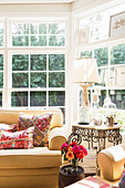 Yellow upholstered furniture with ethnic cushions in the sunny bay window