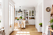 Bright open country-style kitchen with dining area and wooden floor