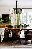 Wicker chairs around the wooden table in the dining room in brown and green