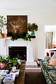 Deer picture and branches on a fireplace console in the living room