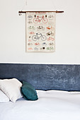 Stripe of chalkboard paint below poster of bicycles on white wall next to bed in child's bedroom