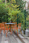 Orange metal chairs and table on wooden deck