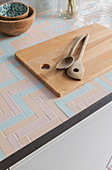 Salad servers and wooden chopping board on kitchen worksurface