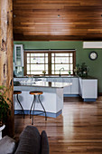 Open kitchen with curved breakfast bar and green wall