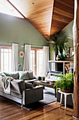 Living room in natural tones with high ceilings and green walls