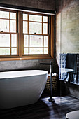Freestanding bathtub in front of lattice windows in the gray bathroom