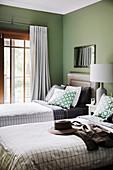 Zwei Einzelbetten im Gästezimmer mit grünen Wänden