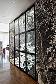 Partition wall covered with black-and-white photo mural and window frames in open-plan interior