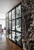 Zwischenwand mit schwarz-weißer Fototapete und Fensterrahmen in offenem Wohnraum