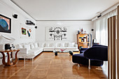 White corner sofa, blue designer sofa and artworks in elegant interior