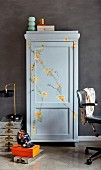 Grey cupboard painted with floral ornaments in study