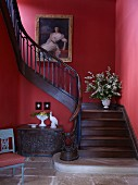 Old trunk below curved wooden staircase with red walls