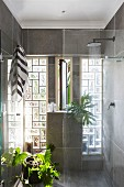 Houseplants in full-width shower with glass-brick wall