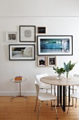 Round table, designer chairs and gallery of pictures on wall