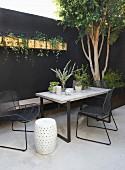 Modern garden furniture in courtyard with black wall