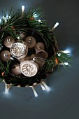 Christmas-tree baubles in dish with fir branches and fairy lights