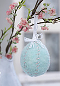 Hand-made, blue, felt Easter egg hung from branch of blossom