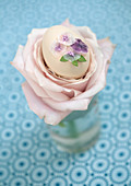 Egg decorated with glittery flowers and nestled in centre of rose