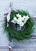 Kranz aus Heidelbeerkraut und weiße Frühlingsblumen an einer Leiter