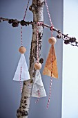 Paper and bead angels hung from branches on baker's twine