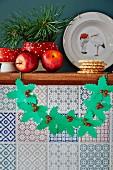 Girlande mit Stechpalmenblättern aus Papier und Beeren aus Perlen