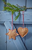 Sewn paper pendants hung from fir branch on blue door