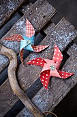 Patterned paper windmills on weathered wooden boards