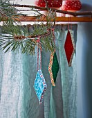 Corrugated paper diamonds with patterned edges hung from branch