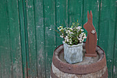 Posy of waxflowers and bunny ornament on wooden barrel
