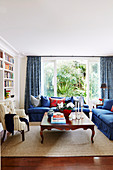 Blue upholstered furniture, antique coffee table and armchair in the living room