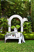 Wooden bench in a well-tended garden, arched in the background