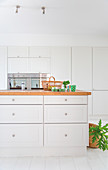 Island counter with white drawer fronts and wooden worksurface in front of fitted cupboards with integrated kitchen appliances
