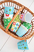 Colourful mugs in wicker basket