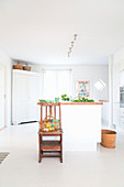 Basket on chair in front of white kitchen island in front of white corner cabinet