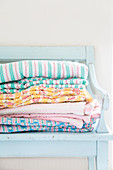 Stacked linen on pale blue wooden bench