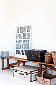 Suitcases, baskets and framed motto on wooden bench