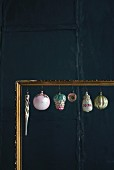 Old Christmas decorations hung in gilt picture frame