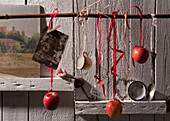 Red apples and old kitchen utensils hung from branch in front of wooden wall