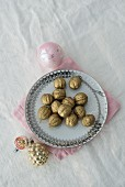 Gold-painted walnuts on ornate plate and Christmas baubles