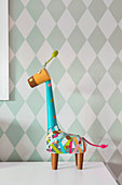 Colorfully painted decorative giraffe against a diamond-patterned wall