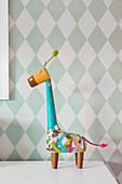 Bunt bemalte Deko-Giraffe vor einer Wand mit Rautenmuster