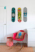 Three skateboards over a red designer rocking chair