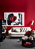 Black coffee table, black cupboard and bright sofa in the living room with red wall